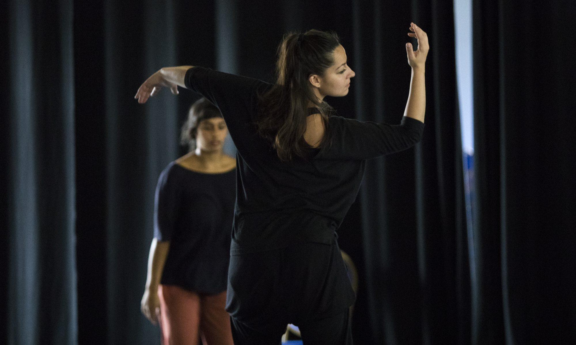 Nadia Iftkhar dancing with her back to the camera, looking over her shoulder with her arms in the air. Her left arm is stretched out to the side and her right arm is bent, with her hand level with her face.