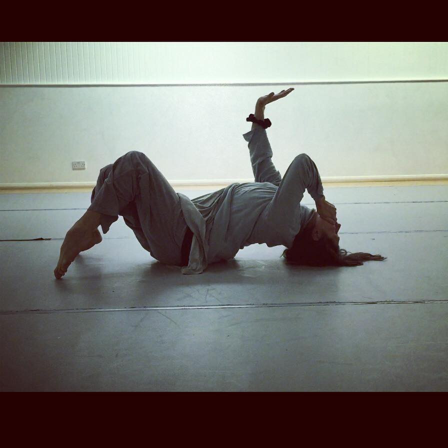 Caroline Reece dancing in rehearsal. She is lying on the floor on her back, with her back arched. One hand is over her mouth, with the other in the air, palm facing the sky. Her legs are bent and her toes are pointed, with only her toes on the floor.