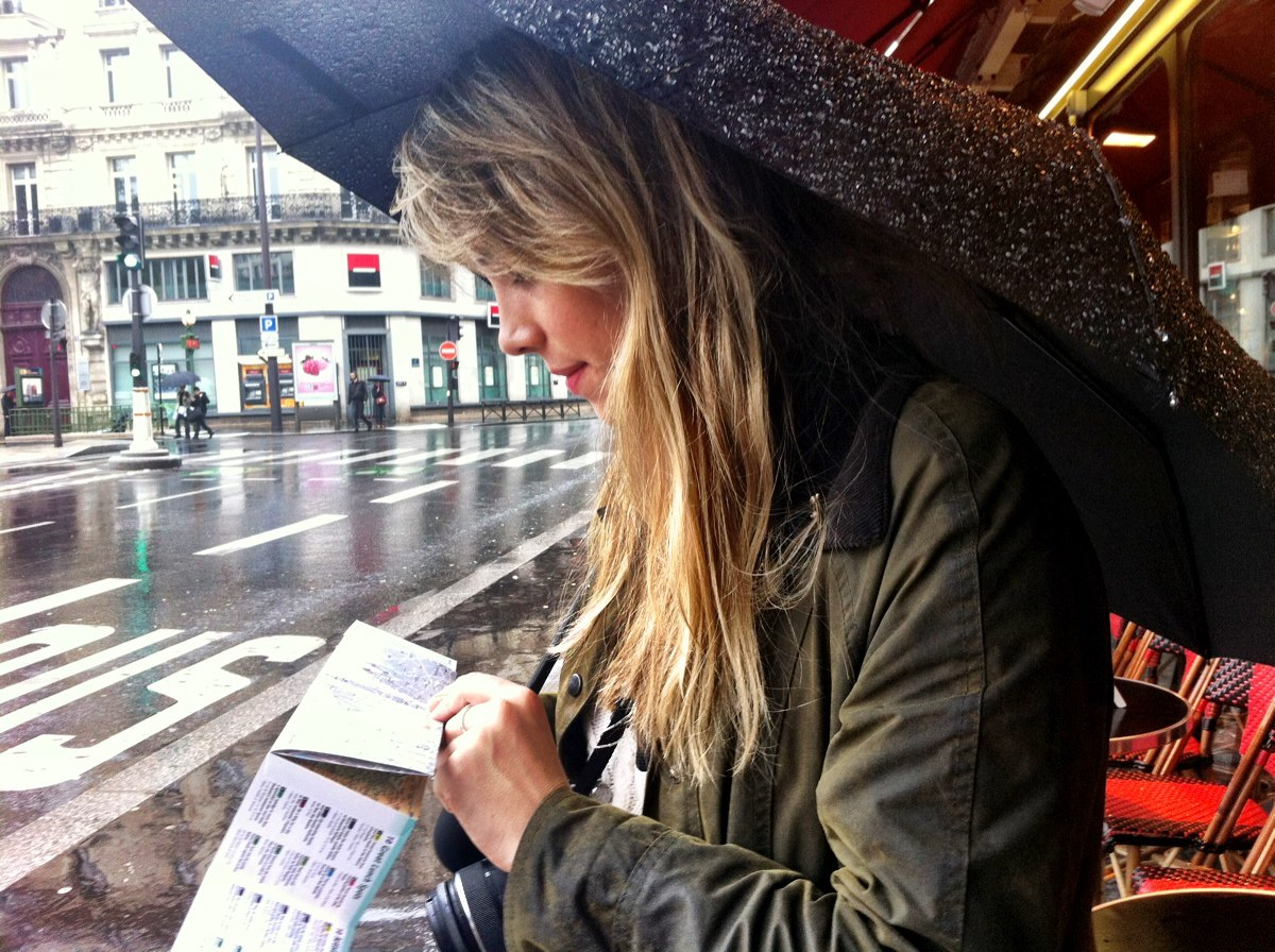 Pippa Howie facing left on a rainy street with an umbrella over her head. She is reading a flyer and wearing a green coat.