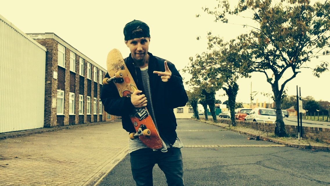 Jamie Michael Korn stood outside in a street. He is holding a skateboard and doing a peace sign for the camera.
