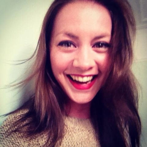 Portait of Molly Hodkinson laughing, facing the camera. She has shoulder length brown hair and is wearing a knitted top.