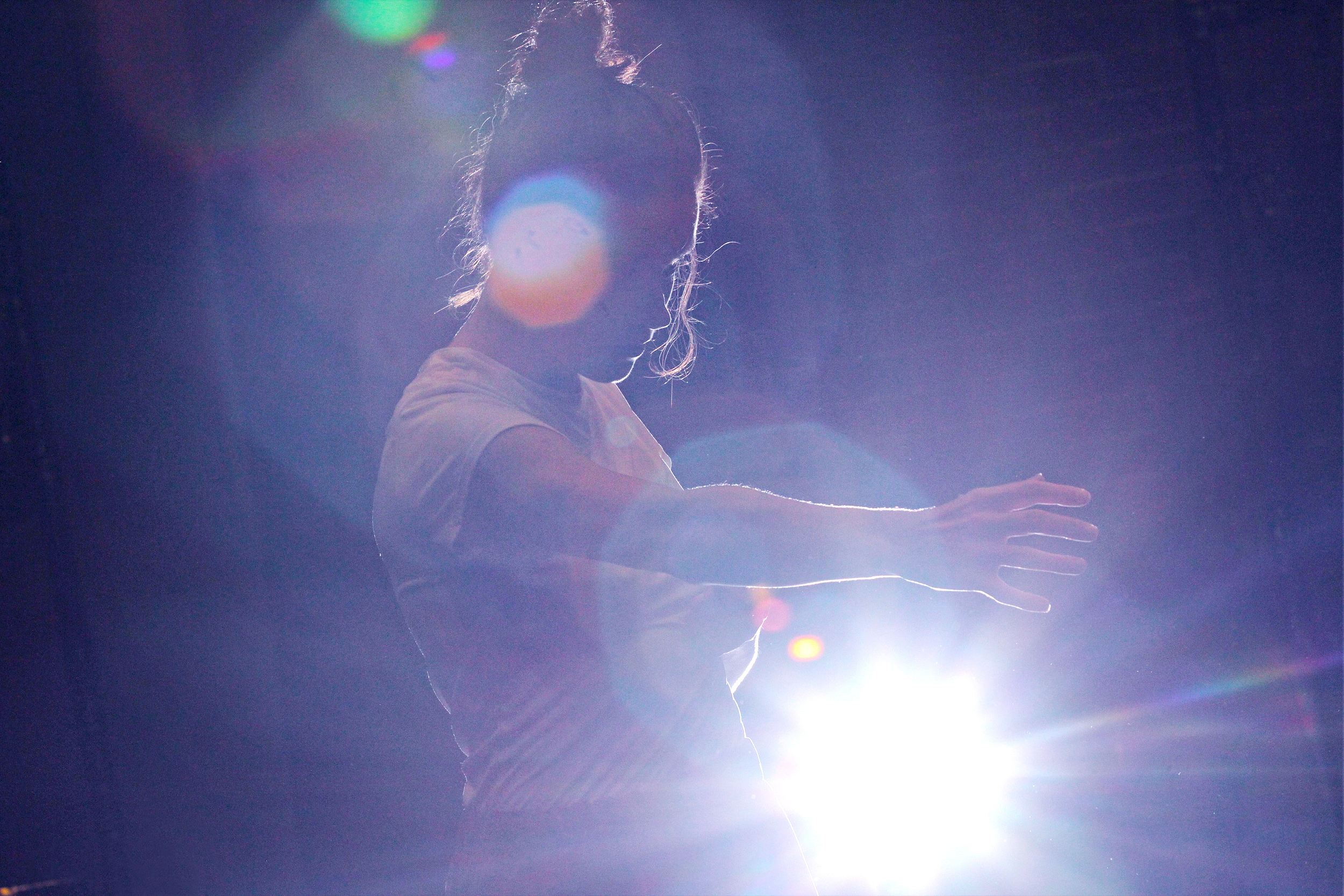 A performer dancing on stage. They are turned to the left, stretching out their right arm. There is a spotlight shining into the camera from behind them.