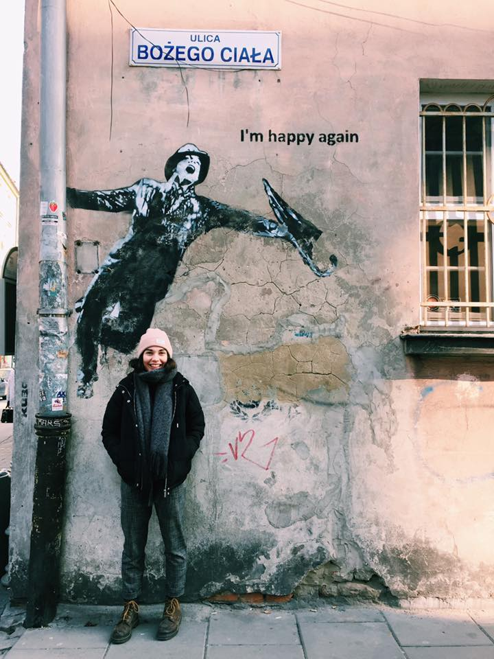 Megan Brown outside, stood in front of streetart by artist Kuba, depicting Gene Kelly dancing in Singing in the Rain. She is smiling and tucking her hands into her pockets.