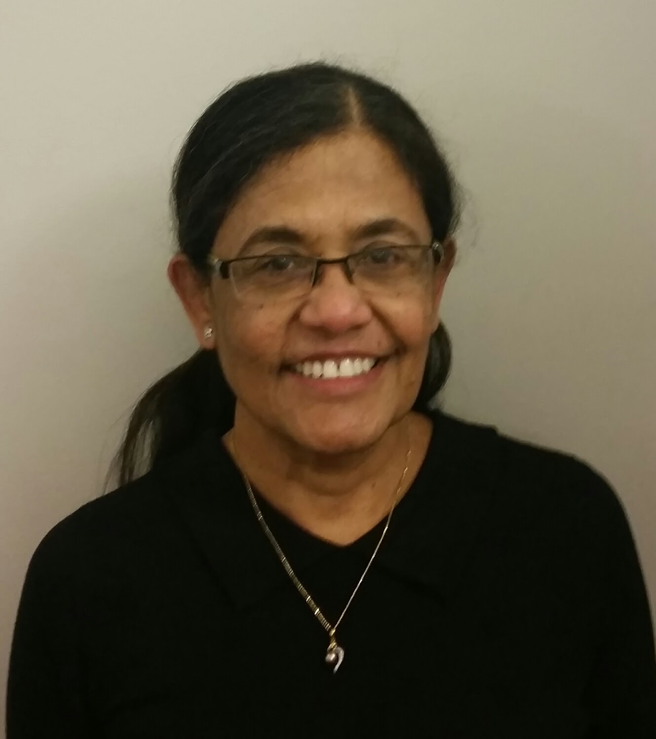 Headshot of Dr Shanta Davie smiling. Her hair is tied back into a ponytail and is wearing glasses and a pendant necklace.