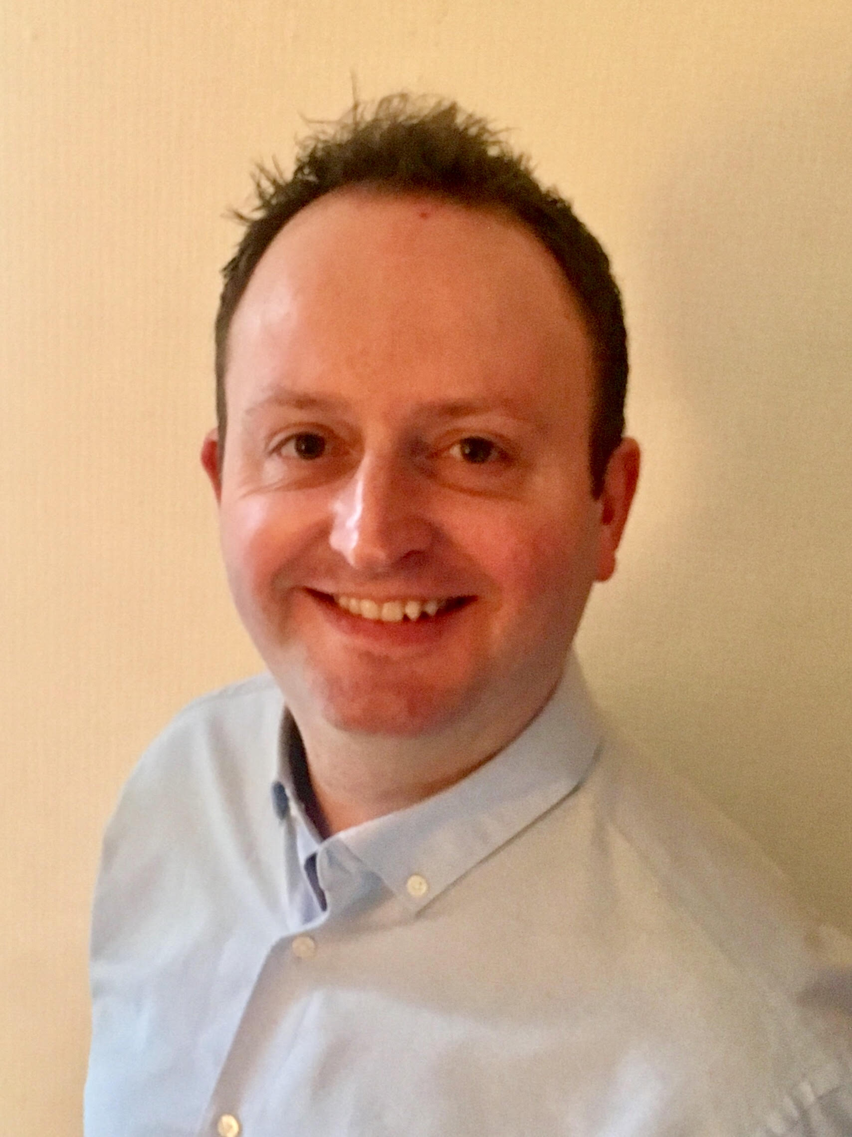 Headshot of Andrew Garrad smiling. He is wearing a blue button up shirt.