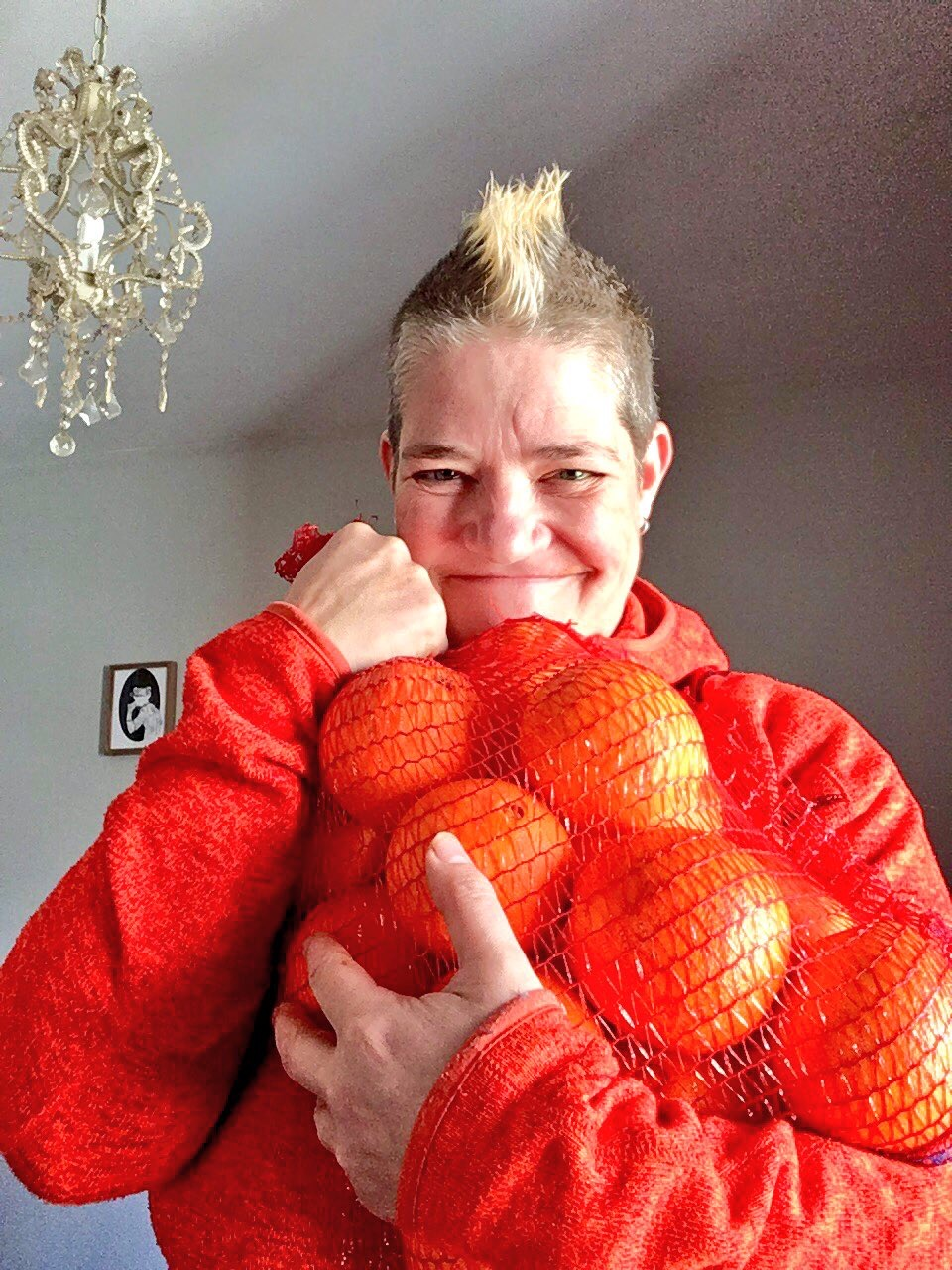 Al Orange smiling at the camera. She has a mohawk, and is holding a big bag of oranges up to her chest. She is in a room with a chandelier and a framed piece of artwork behind her.