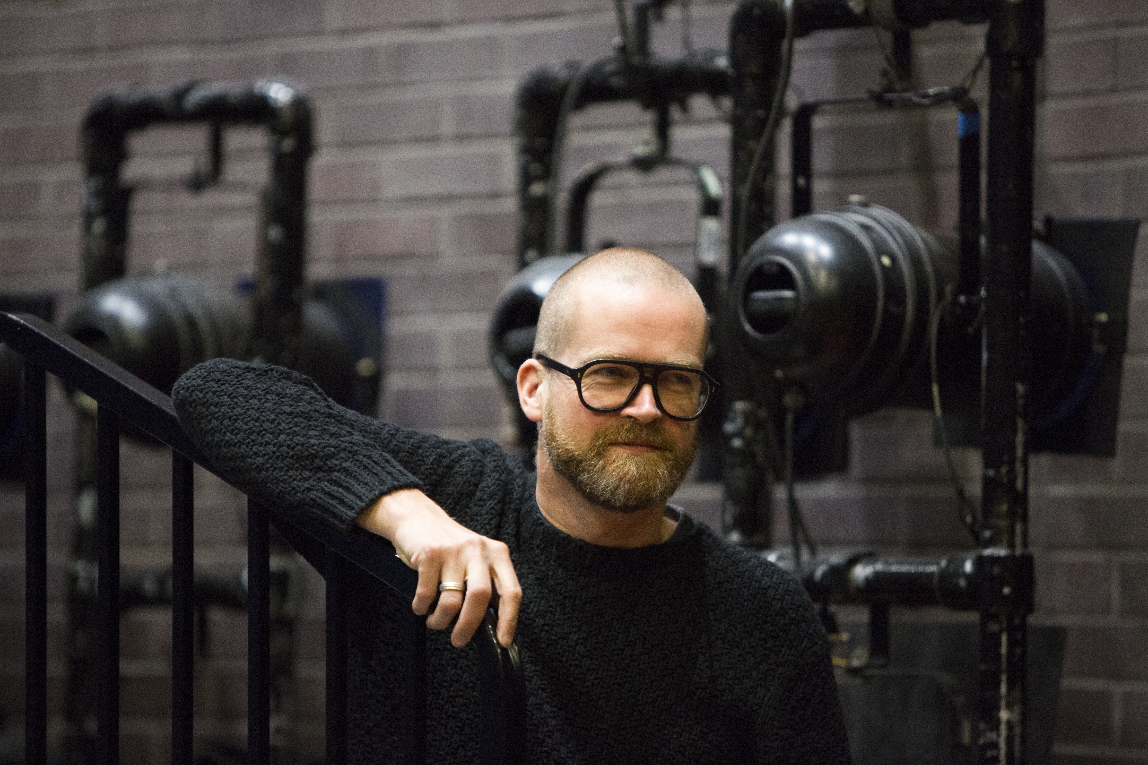 Nicolai Hart-Handsen leaning on a stair railing. Behind him is theatre technical equipment. He is wearing big, thick rimmed glasses and has a short beard.