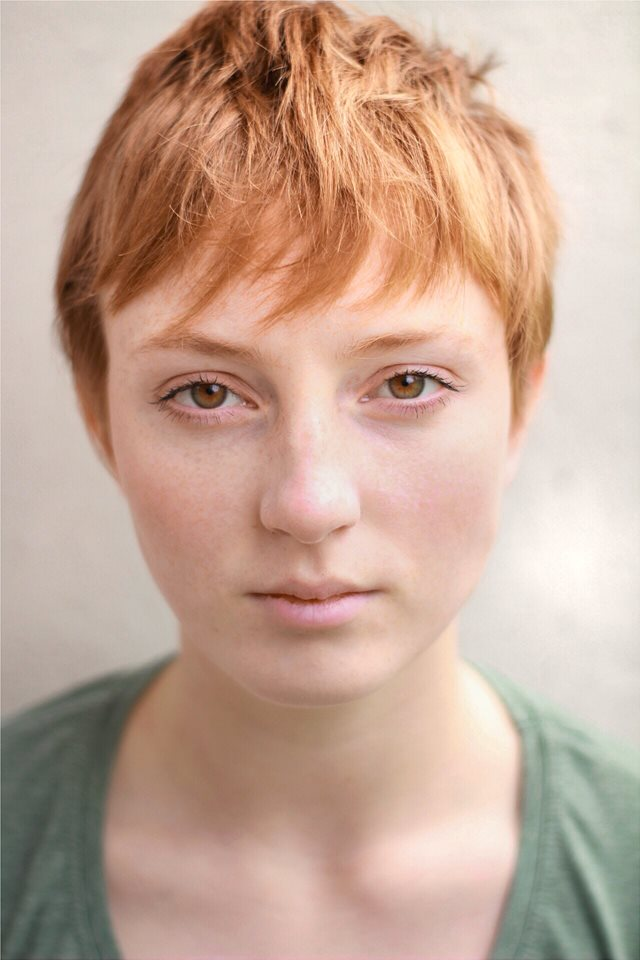 Headshot of Emma Holt outside, facing the camera. She has short hair, and is wearing a green top.