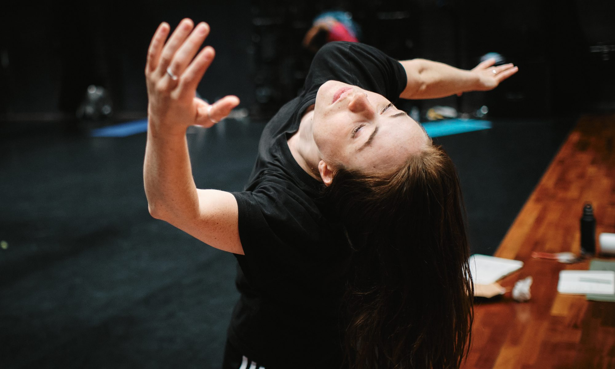 Alicia Meehan dancing. The picture is taken from a high angle, angled down at her face which is falling back. Her right arm twisting out to the side and her left arm stretching up towards the camera.
