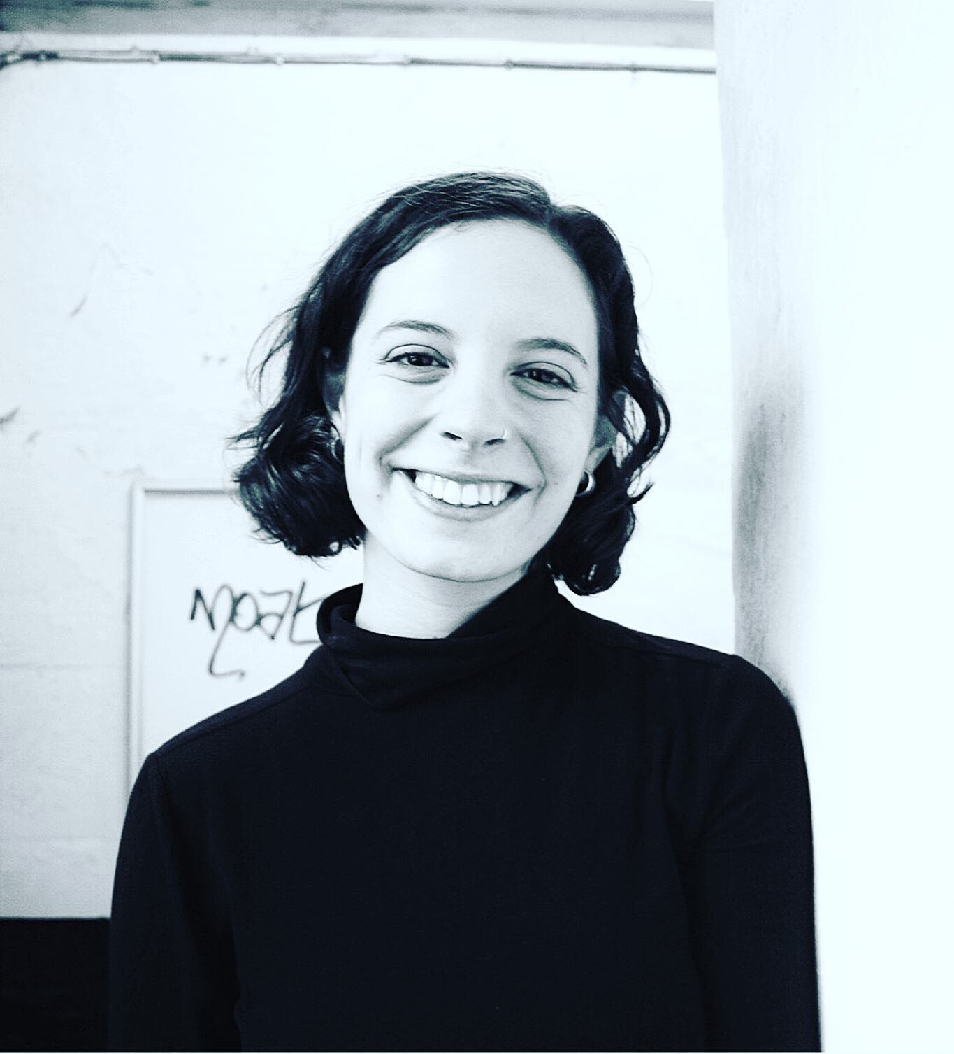 Black and white headshot of Jenny Crisp. She is smiling at the camera, and wearing her hair in a short bob.