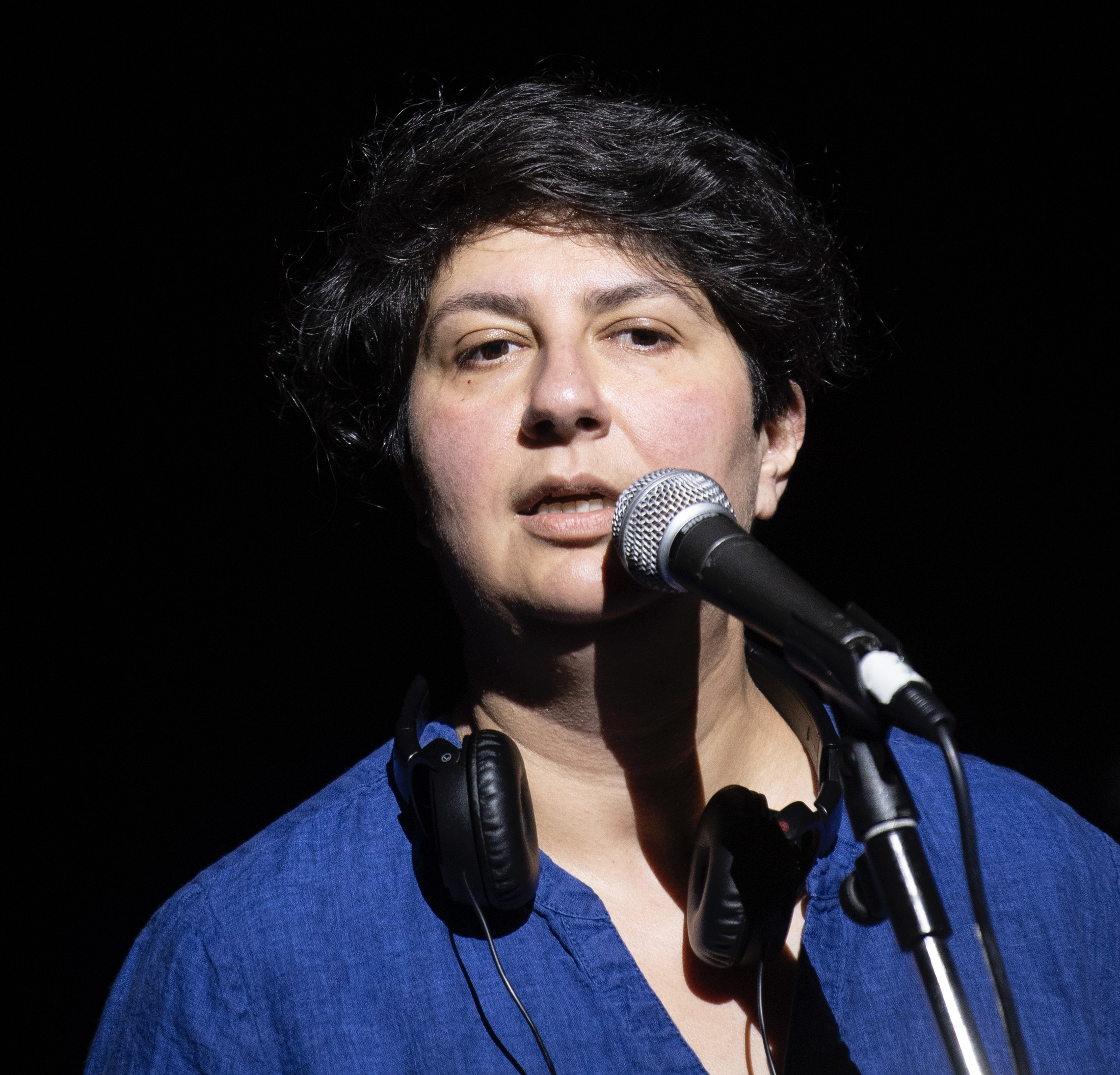 Nazli Tabatabai-Khatambakhsh standing at a microphone. She has over ear headphones around her neck.