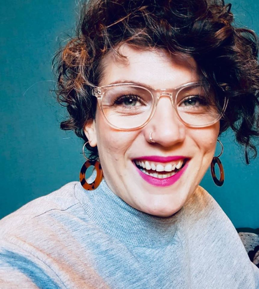Kim Simpson smiling. She has short curly hair, clear rimmed glasses, dangly hoop earrings and is wearing bright pink lipstick.