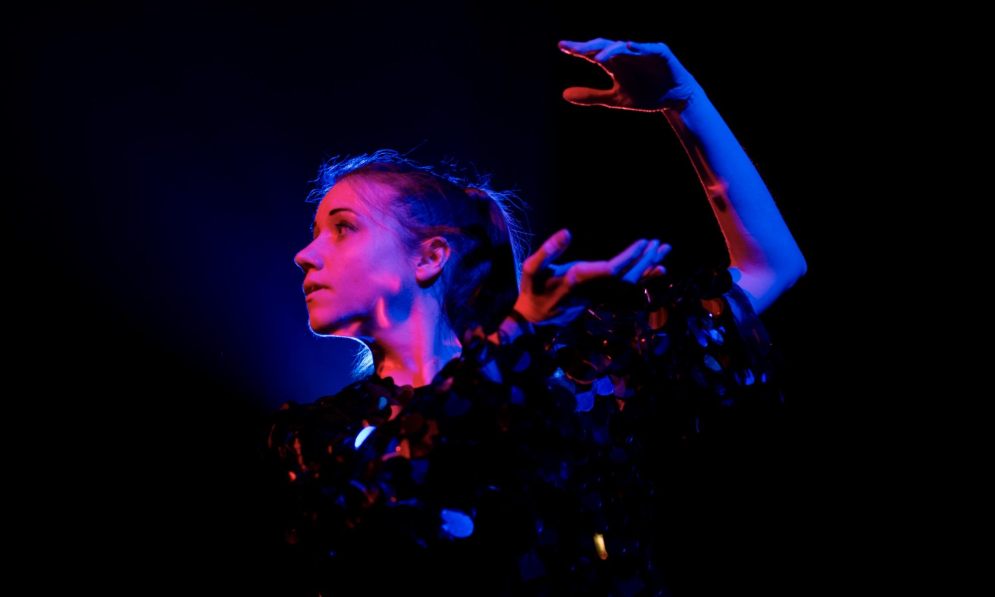 Jem Clancy dancing on stage. Her arm is up high behind her. She is lit by purple, pink and blue lighting.