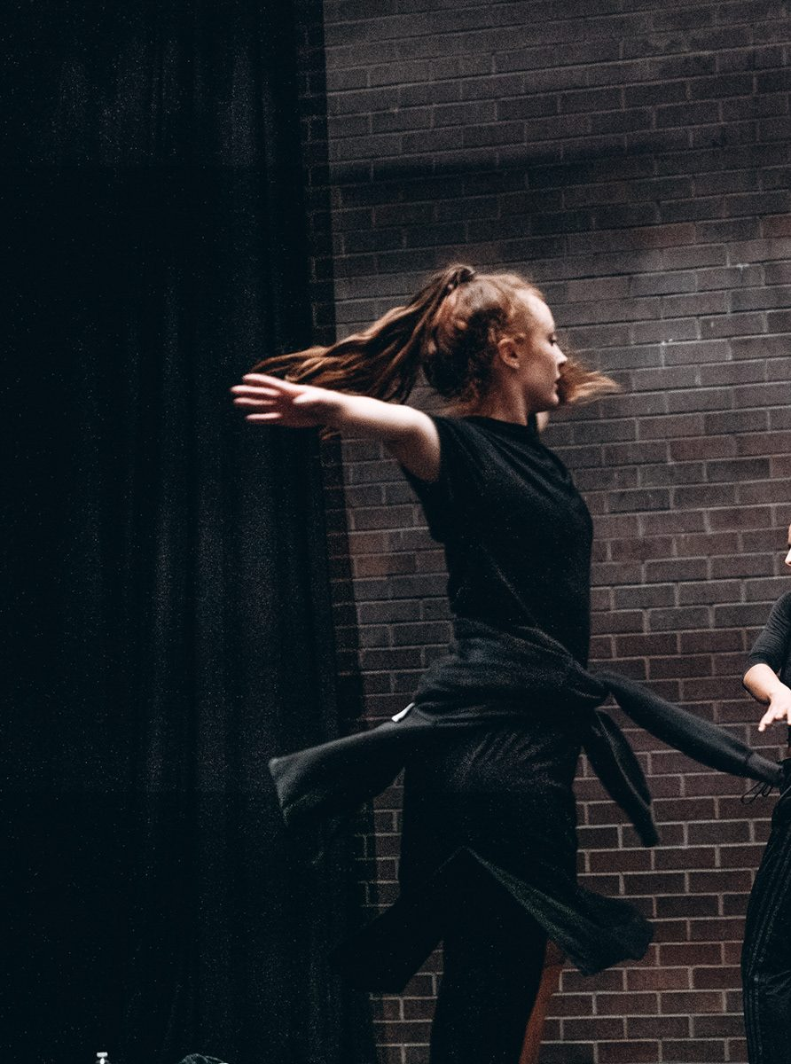 Cora-Jay Williams dancing in rehearsal. She is spinning, with her arms stretched out wide. Her hair and the hoody she has tied around her waist are in the air from the momentum.