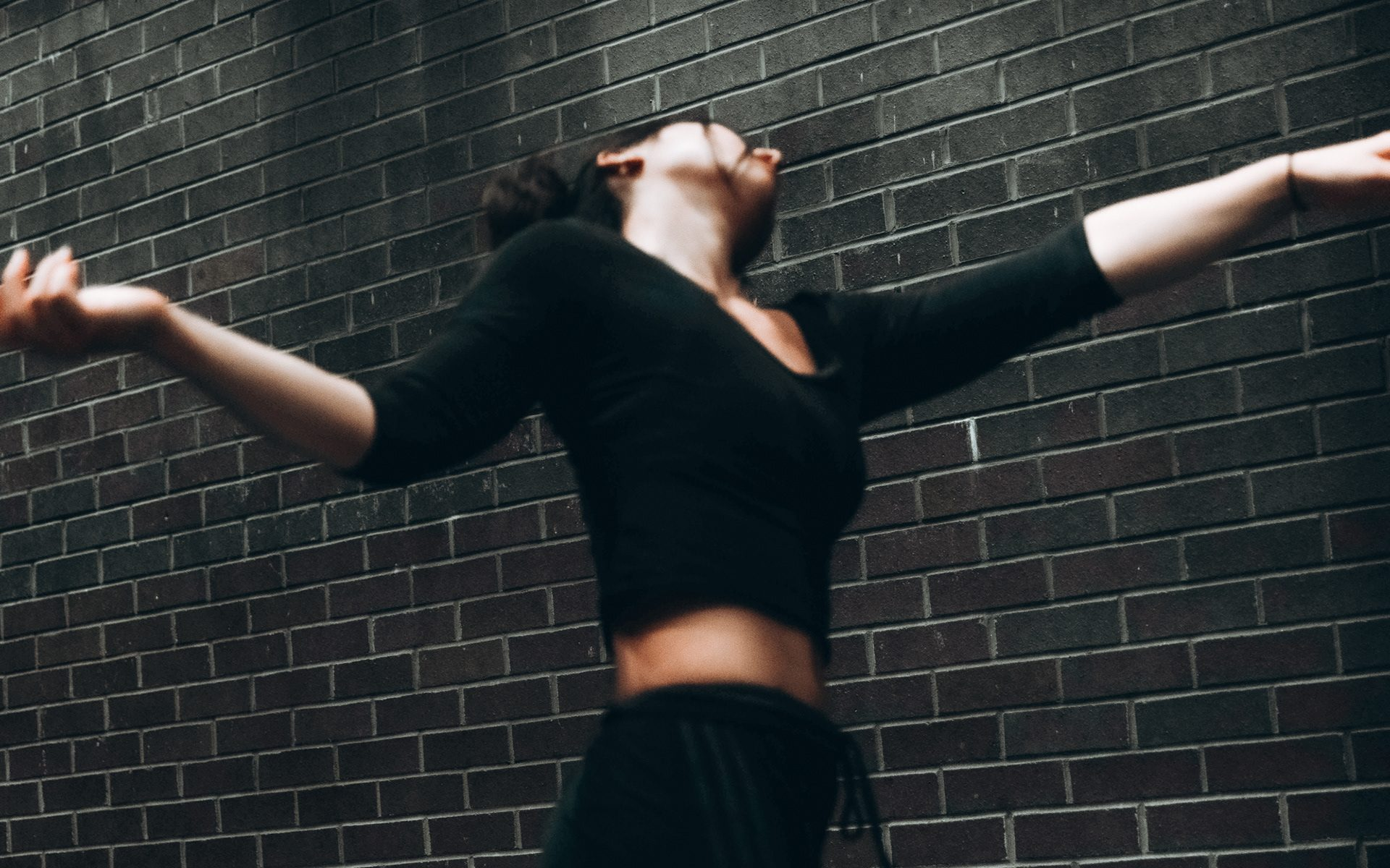 Lila from a low angle, dancing in front of a dark brick wall. Her arms are stretched out to her side, her head turned away from the camera.
