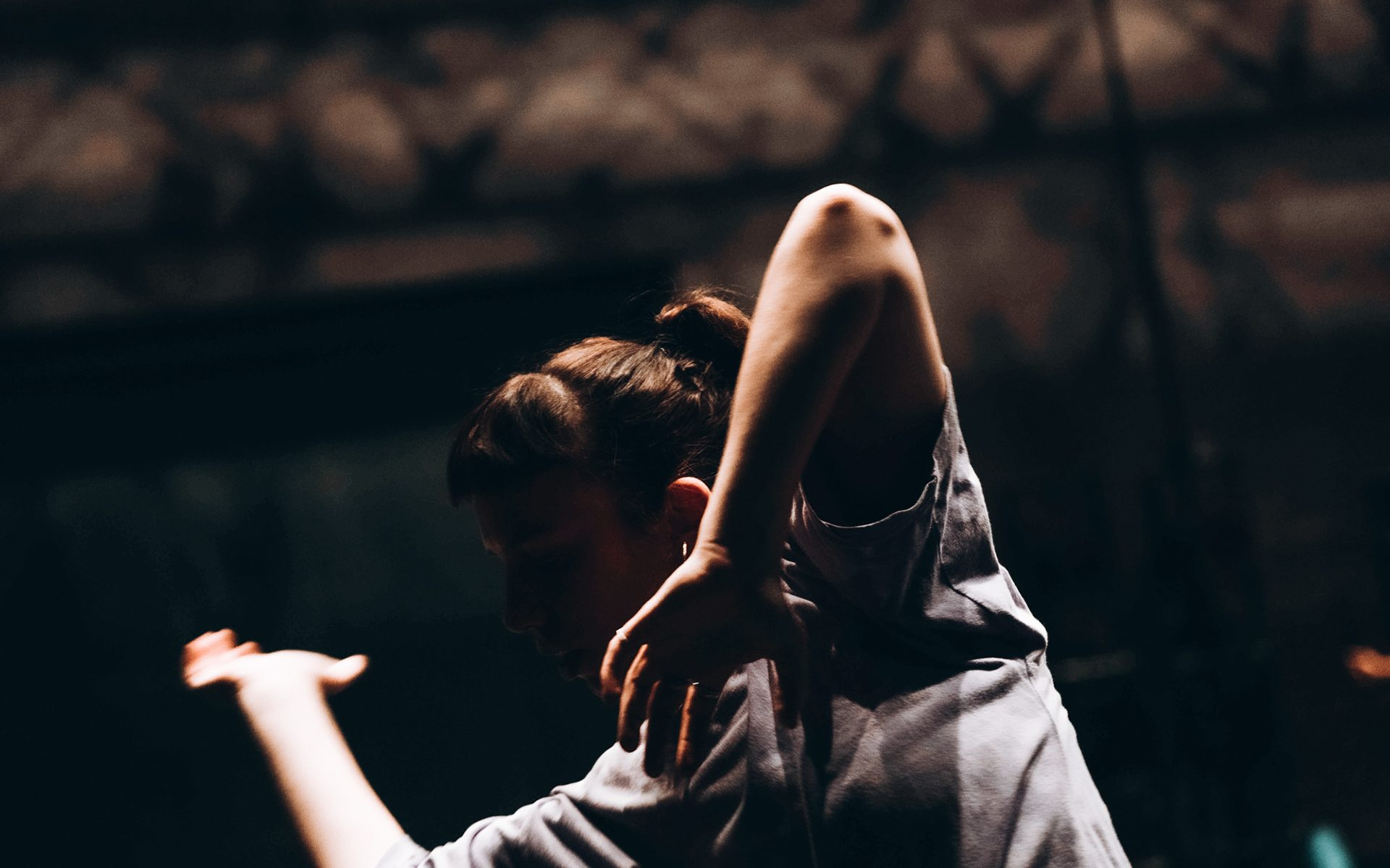 Alyssa Lisle dancing. Her face is in the dark and her arms are bent, one next to her head and one stretching out.