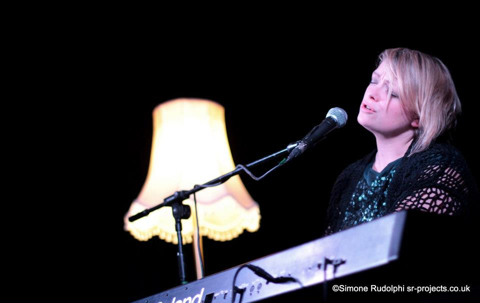 Beccy Owen performing on stage. She is playing a keyboard, singing into a microphone. Behind her is a lamp that is turned on.