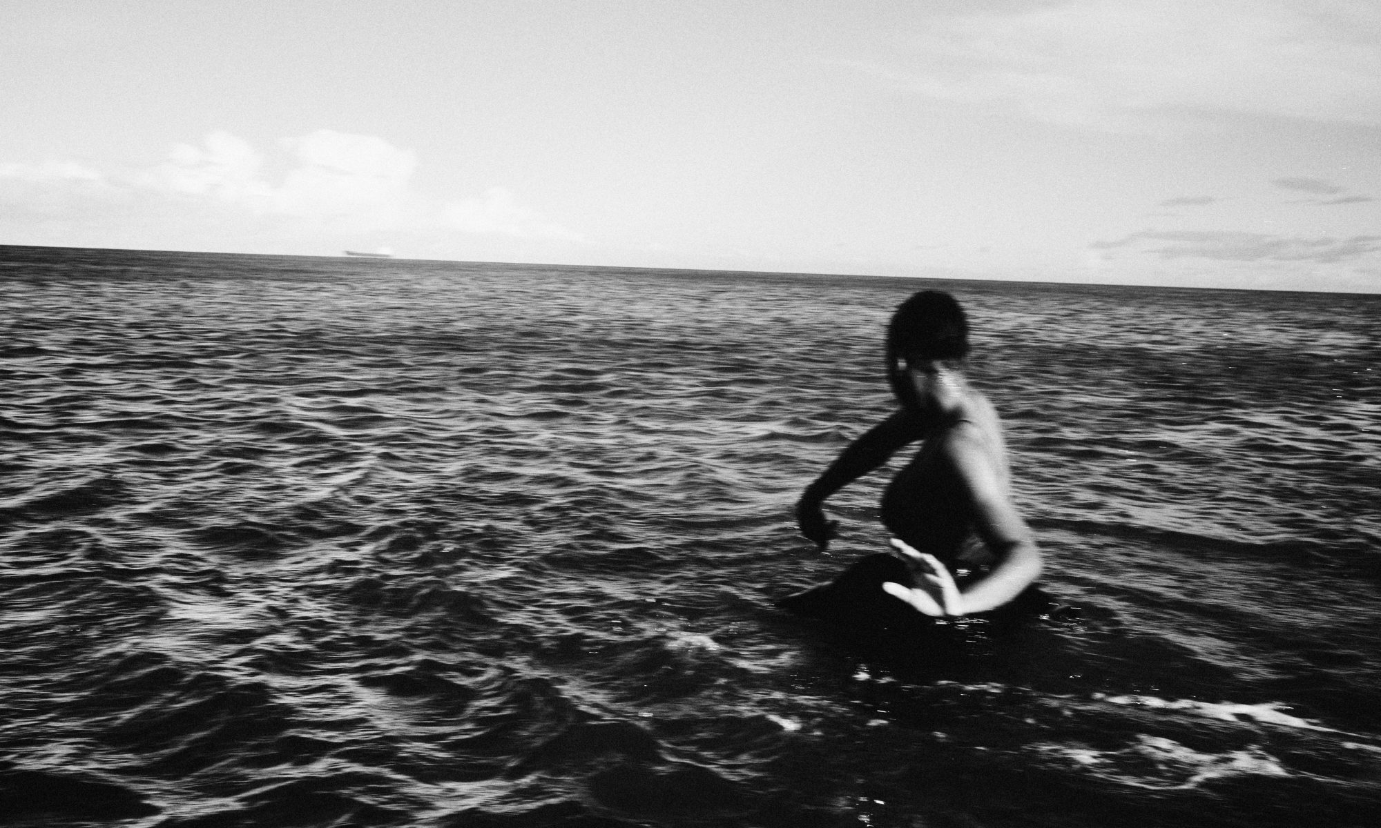 Black and white picture of three performers waist deep in the ocean. Water splashes up as they move and dance in the ocean.