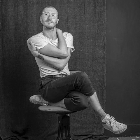 Black and white portrait of Phillip Brown sat on a stool. One leg is bent underneath him with the other crossed on top of it. He's holding his body with his arms.